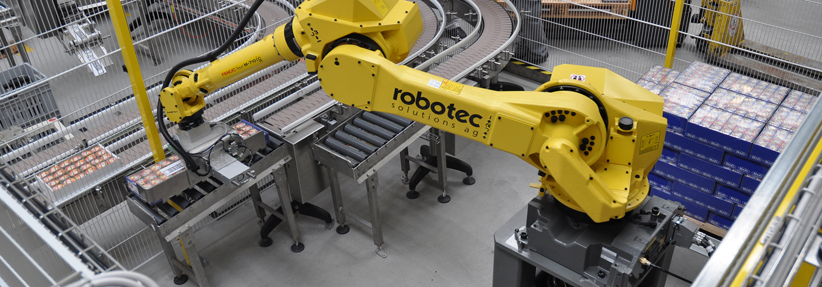 Robot M-710iC placing food carriers onto conveyor belt